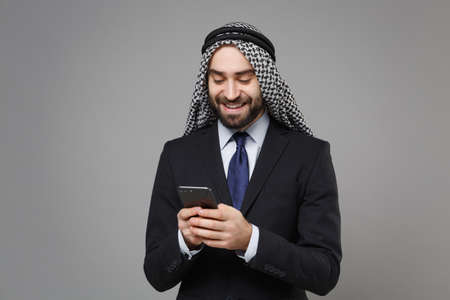 Smiling arabian muslim businessman in keffiyeh kafiya ring igal agal classic black suit isolated on gray background. Achievement career wealth business concept. Using mobile phone, typing sms message. Banco de Imagens