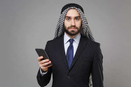 Bearded arabian muslim businessman in keffiyeh kafiya ring igal agal classic black suit isolated on gray background. Achievement career wealth business concept. Using mobile phone, typing sms message.