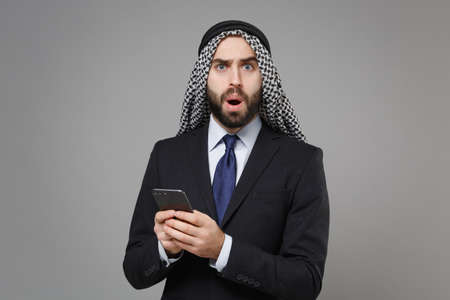 Shocked arabian muslim businessman in keffiyeh kafiya ring igal agal classic black suit isolated on gray background. Achievement career wealth business concept. Using mobile phone, typing sms message.
