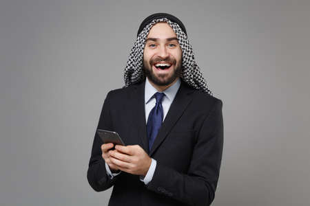Cheerful arabian muslim businessman in keffiyeh kafiya ring igal agal classic black suit isolated on gray background. Achievement career wealth business concept. Using mobile phone typing sms message. Banco de Imagens