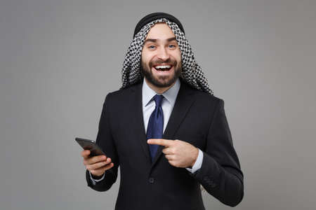 Funny arabian muslim businessman in keffiyeh kafiya ring igal agal classic black suit isolated on gray background. Achievement career wealth business concept. Pointing index finger on mobile phone.
