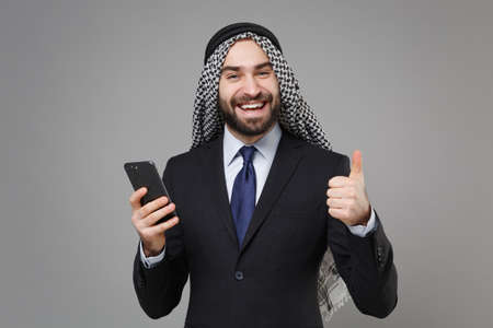 Joyful arabian muslim businessman in keffiyeh kafiya ring igal agal classic black suit isolated on gray background. Achievement career wealth business concept. Hold mobile phone, showing thumb up.