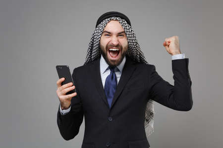 Happy arabian muslim businessman in keffiyeh kafiya ring igal agal classic black suit isolated on gray background. Achievement career wealth business concept. Hold mobile phone, doing winner gesture. Banco de Imagens