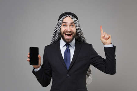 Excited arabian muslim businessman in keffiyeh kafiya ring igal agal suit isolated on gray background. Achievement career wealth business concept. Hold mobile phone with empty screen point finger up.