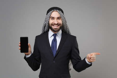 Joyful arabian muslim businessman in keffiyeh kafiya ring igal agal suit isolated on gray background. Achievement career wealth business concept Hold mobile phone with blank screen point finger aside. Banco de Imagens