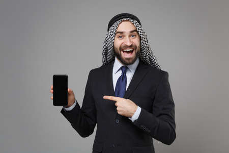 Excited arabian muslim businessman in keffiyeh kafiya ring igal agal suit isolated on gray background. Achievement career wealth business concept. Point finger on mobile phone with blank empty screen. Banco de Imagens