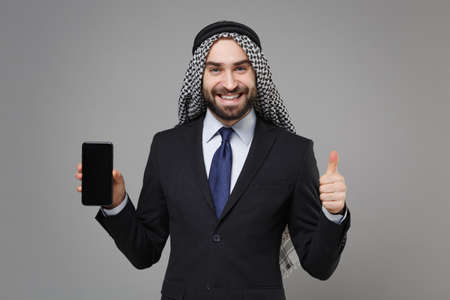 Smiling arabian muslim businessman in keffiyeh kafiya ring igal agal suit isolated on gray background. Achievement career wealth business concept Hold mobile phone with blank screen showing thumb up.
