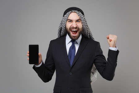 Happy arabian muslim businessman in keffiyeh kafiya ring igal agal isolated on gray background. Achievement career wealth business concept. Hold mobile phone with empty screen doing winner gesture. Banco de Imagens