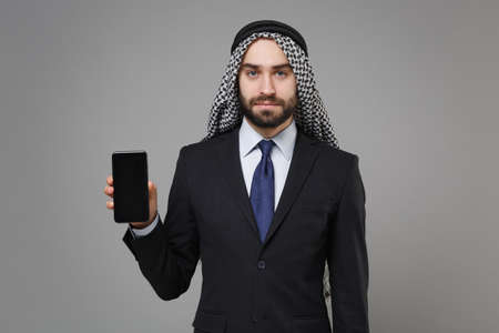 Handsome bearded arabian muslim businessman in keffiyeh kafiya ring igal agal suit isolated on gray background. Achievement career wealth business concept. Hold mobile phone with blank empty screen. Banco de Imagens