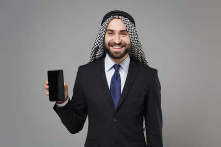 Smiling bearded arabian muslim businessman in keffiyeh kafiya ring igal agal suit isolated on gray background. Achievement career wealth business concept. Hold mobile phone with blank empty screen.