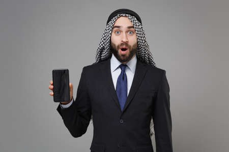Shocked bearded arabian muslim businessman in keffiyeh kafiya ring igal agal suit isolated on gray background. Achievement career wealth business concept. Hold mobile phone with blank empty screen.