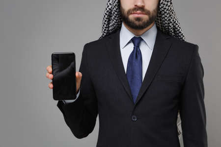 Cropped image of arabian muslim businessman in keffiyeh kafiya ring igal agal suit isolated on gray background. Achievement career wealth business concept. Hold mobile phone with blank empty screen.