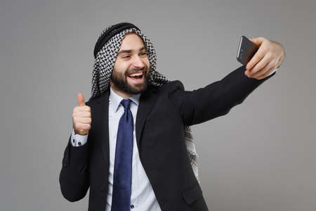 Cheerful arabian muslim businessman in keffiyeh kafiya ring igal agal suit isolated on gray background. Achievement career wealth business concept. Doing selfie shot on mobile phone showing thumb up.