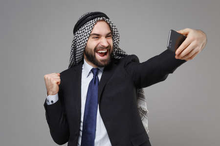 Happy arabian muslim businessman in keffiyeh kafiya ring igal agal suit isolated on gray background. Achievement career wealth business concept. Doing selfie shot on mobile phone doing winner gesture.