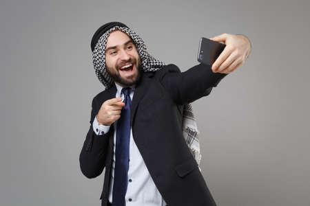 Arabian muslim businessman in keffiyeh kafiya ring igal agal suit isolated on gray background. Achievement career wealth business concept. Doing selfie shot on mobile phone pointing finger on camera.