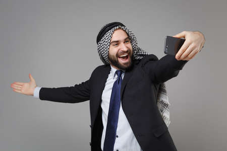 Cheerful arabian muslim businessman in keffiyeh kafiya ring igal agal suit isolated on gray background. Achievement career wealth business concept. Doing selfie shot on mobile phone spreading hands.