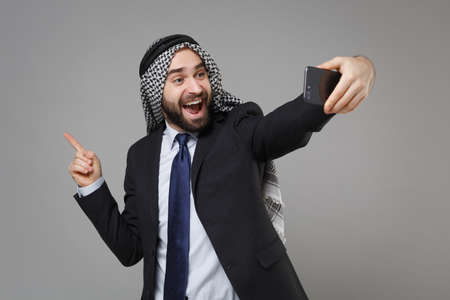 Excited arabian muslim businessman in keffiyeh kafiya ring igal agal suit isolated on gray background. Achievement career wealth business concept. Doing selfie shot on mobile phone point finger aside.
