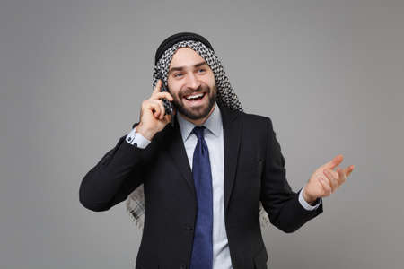 Cheerful bearded arabian muslim businessman in keffiyeh kafiya ring igal agal classic black suit shirt isolated on gray background. Achievement career wealth business concept. Talking on mobile phone.