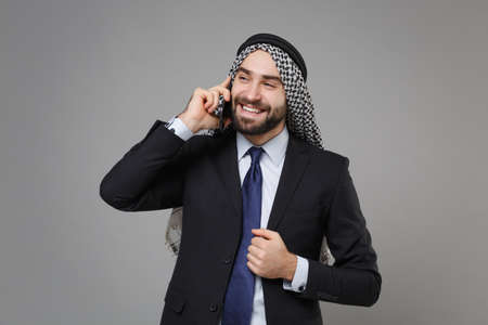 Smiling bearded arabian muslim businessman in keffiyeh kafiya ring igal agal classic black suit shirt isolated on gray background. Achievement career wealth business concept. Talking on mobile phone.