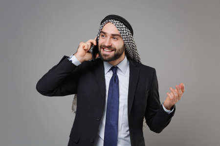 Handsome bearded arabian muslim businessman in keffiyeh kafiya ring igal agal classic black suit shirt isolated on gray background. Achievement career wealth business concept. Talking on mobile phone.