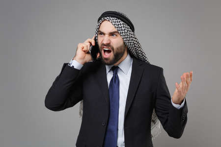 Angry bearded arabian muslim businessman in keffiyeh kafiya ring igal agal classic black suit isolated on gray background. Achievement career wealth business concept. Talk on mobile phone screaming.