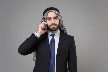 Serious bearded arabian muslim businessman in keffiyeh kafiya ring igal agal classic black suit shirt isolated on gray background. Achievement career wealth business concept. Talking on mobile phone.