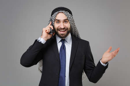 Funny bearded arabian muslim businessman in keffiyeh kafiya ring igal agal classic black suit shirt isolated on gray background. Achievement career wealth business concept. Talking on mobile phone.