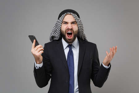 Irritated bearded arabian muslim businessman in keffiyeh kafiya ring igal agal classic black suit isolated on gray background. Achievement career wealth business concept. Talk on mobile phone scream.