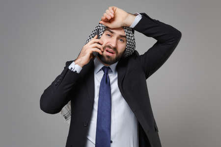 Tired bearded arabian muslim businessman in keffiyeh kafiya ring igal agal classic black suit shirt isolated on gray background. Achievement career wealth business concept. Talking on mobile phone.