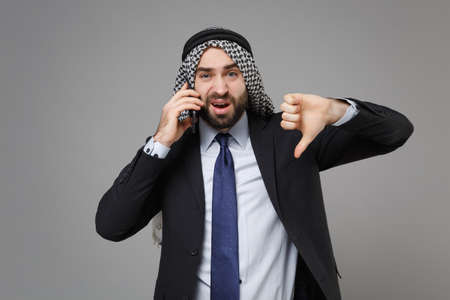 Displeased arabian muslim businessman in keffiyeh kafiya ring igal agal black suit isolated on gray background. Achievement career wealth business concept. Talking on mobile phone showing thumb down. Standard-Bild