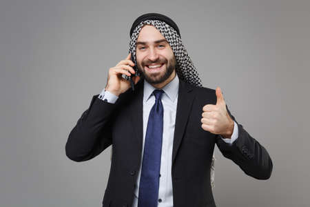 Smiling bearded arabian muslim businessman in keffiyeh kafiya ring igal agal black suit isolated on gray background. Achievement career wealth business concept. Talk on mobile phone showing thumb up.