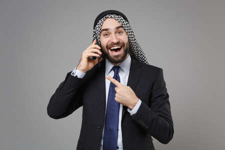 Excited bearded arabian muslim businessman in keffiyeh kafiya ring igal agal black suit isolated on gray background. Achievement career wealth business concept. Talk on mobile phone, pointing finger.
