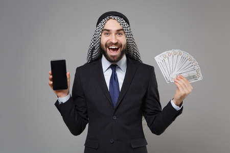 Excited arabian muslim businessman in keffiyeh kafiya ring igal agal suit isolated on gray background. Achievement career wealth business . Hold mobile phone with blank empty screen fan of cash money.