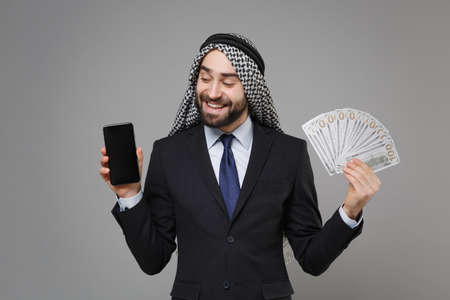 Smiling arabian muslim businessman in keffiyeh kafiya ring igal agal suit isolated on gray background. Achievement career wealth business . Hold mobile phone with blank empty screen fan of cash money.