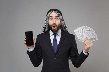 Shocked arabian muslim businessman in keffiyeh kafiya ring igal agal suit isolated on gray background. Achievement career wealth business . Hold mobile phone with blank empty screen fan of cash money. Standard-Bild