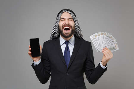 Laughing arabian muslim businessman in keffiyeh kafiya ring igal agal suit isolated on gray background. Achievement career wealth business. Hold mobile phone with blank empty screen fan of cash money. Standard-Bild