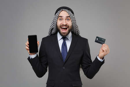 Excited arabian muslim businessman in keffiyeh kafiya ring igal agal suit isolated on gray background. Achievement career wealth business. Hold mobile phone with blank empty screen credit bank card.
