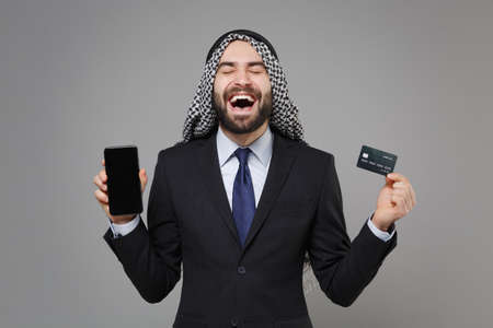 Overjoyed arabian muslim businessman in keffiyeh kafiya ring igal agal suit isolated on gray background. Achievement career wealth business. Hold mobile phone with blank empty screen credit bank card.