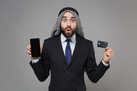 Shocked arabian muslim businessman in keffiyeh kafiya ring igal agal suit isolated on gray background. Achievement career wealth business. Hold mobile phone with blank empty screen credit bank card. Standard-Bild