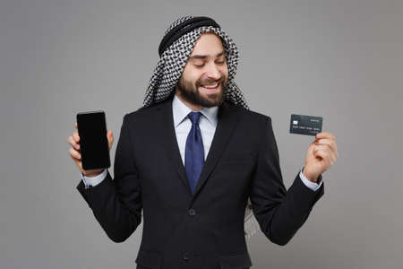Smiling arabian muslim businessman in keffiyeh kafiya ring igal agal suit isolated on gray background. Achievement career wealth business. Hold mobile phone with blank empty screen credit bank card.