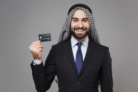 Smiling bearded arabian muslim businessman in keffiyeh kafiya ring igal agal classic black suit shirt isolated on gray background. Achievement career wealth business concept. Hold credit bank card.