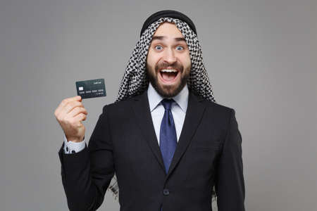 Surprised bearded arabian muslim businessman in keffiyeh kafiya ring igal agal classic black suit shirt isolated on gray background. Achievement career wealth business concept. Hold credit bank card.