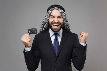 Joyful arabian muslim businessman in keffiyeh kafiya ring igal agal classic suit isolated on gray background. Achievement career wealth business concept. Hold credit bank card doing winner gesture. Banco de Imagens