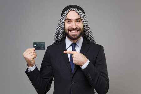 Smiling arabian muslim businessman in keffiyeh kafiya ring igal agal classic suit isolated on gray background. Achievement career wealth business concept. Pointing index finger on credit bank card.