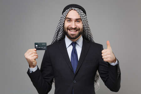 Smiling arabian muslim businessman in keffiyeh kafiya ring igal agal classic suit shirt isolated on gray background. Achievement career wealth business concept. Hold credit bank card showing thumb up. Banco de Imagens