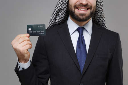 Cropped image of smiling arabian muslim businessman in keffiyeh kafiya ring igal agal classic black suit isolated on gray background. Achievement career wealth business concept. Hold credit bank card.