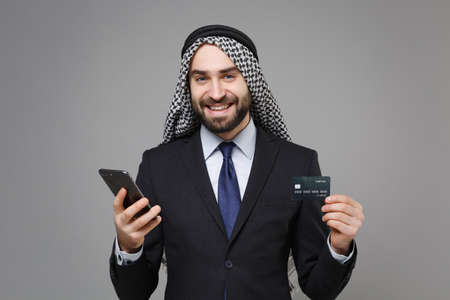 Smiling bearded arabian muslim businessman in keffiyeh kafiya ring igal agal classic suit isolated on gray background. Achievement career wealth business concept. Hold mobile phone, credit bank card.