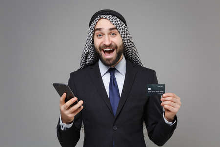 Excited bearded arabian muslim businessman in keffiyeh kafiya ring igal agal classic suit isolated on gray background. Achievement career wealth business concept. Hold mobile phone, credit bank card.