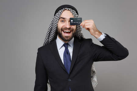 Funny young arabian muslim businessman in keffiyeh kafiya ring igal agal classic suit shirt isolated on gray background. Achievement career wealth business concept. Covering eye with credit bank card. Standard-Bild