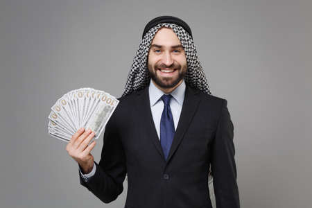 Smiling bearded arabian muslim businessman in keffiyeh kafiya ring igal agal suit isolated on gray background. Achievement career wealth business concept. Hold fan of cash money in dollar banknotes.